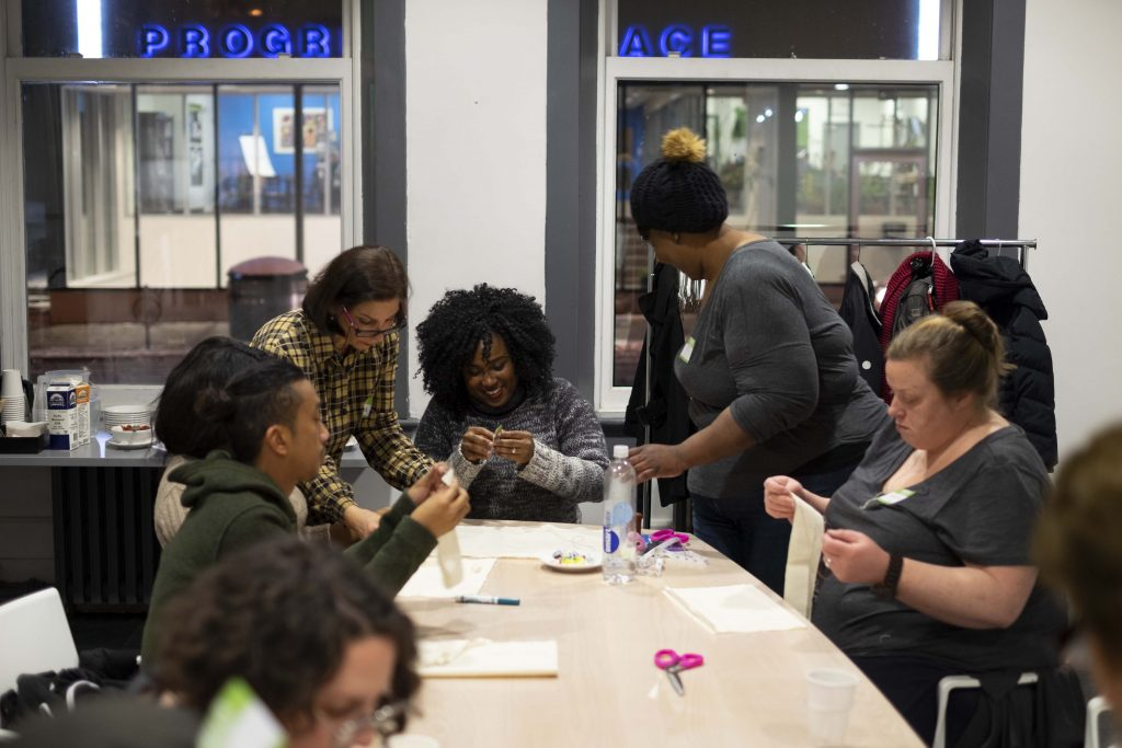 A group of participants around a table sewing with their hands.