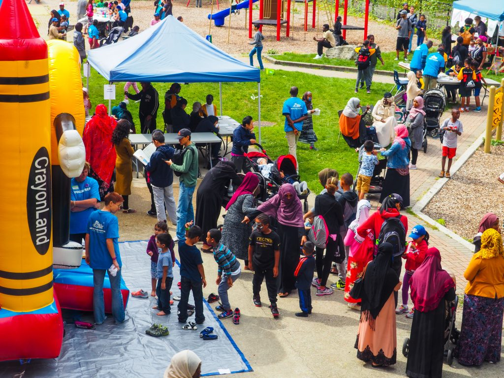 Scene from the park with children and families standing around a bouncy castle at Regent Park