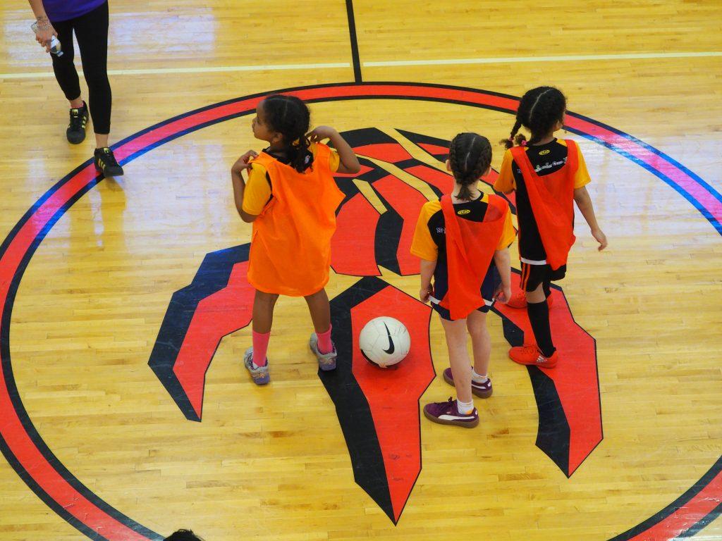 Three children in sports wear on an indoor gym field.
