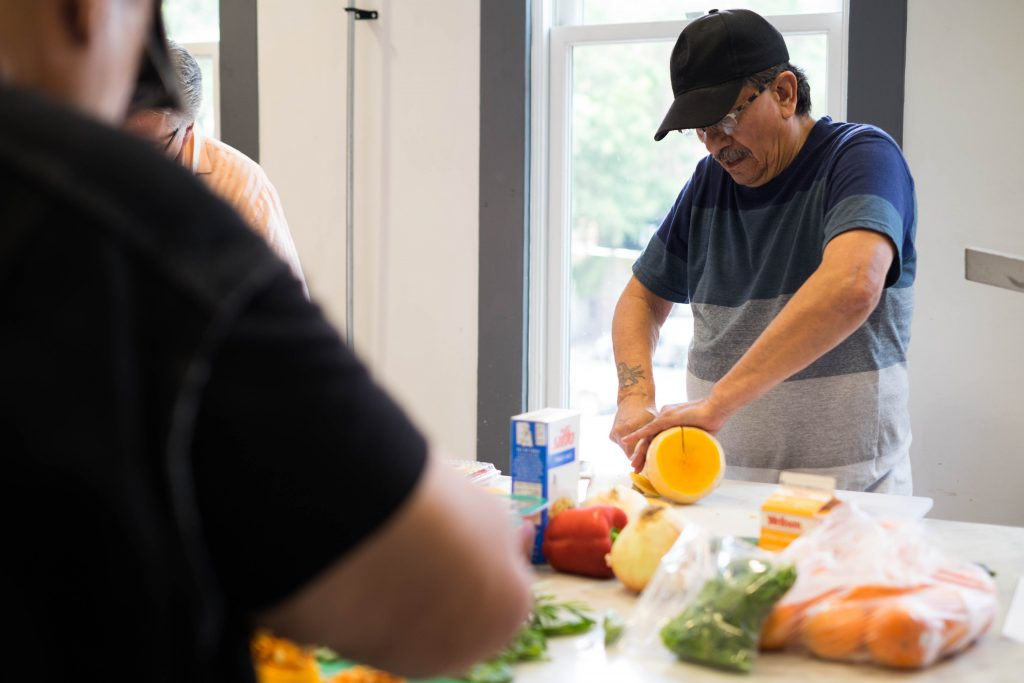Photo of a person chopping vegetables in a community kitchen.