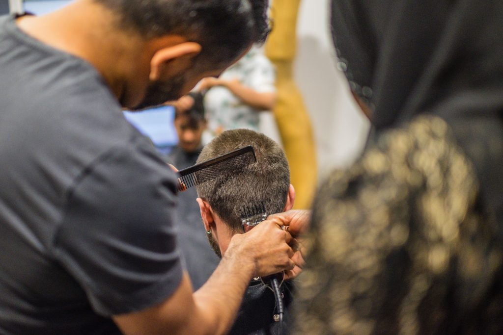 Photo from the back of a barber cutting a person's hair as a trainee looks on.