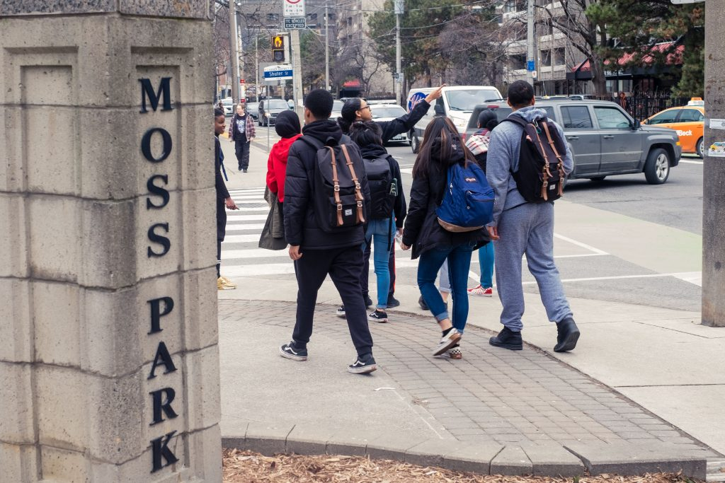 A group of youth with backpacks walking alongside Moss Park sign